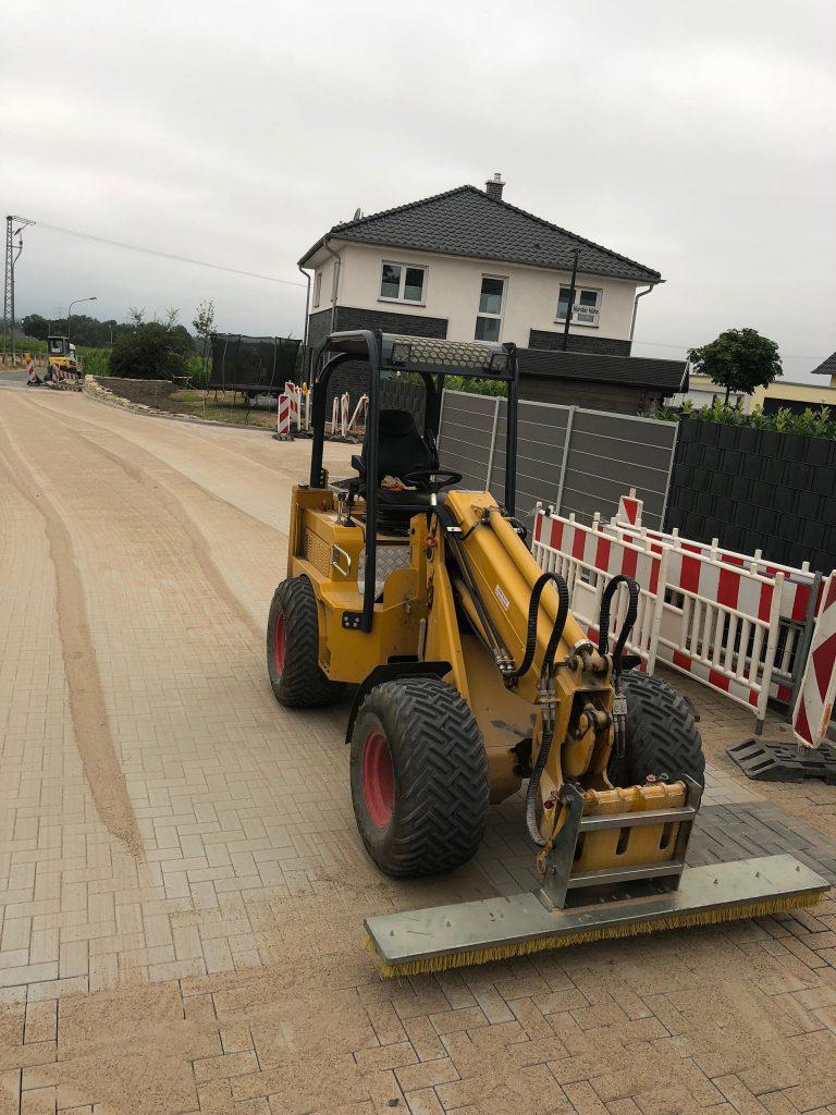 Halimi Pflasterbau Projekt Bagger führt Pflasterarbeiten auf einer Straße durch